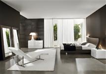 Cette chambre très épurée marie le blanc et le marron. Ce choix lui confère un côté fort masculin renforcé par le minimalisme du mobilier présent dans la pièce. Espace très design réchauffé par d'amples tentures qui caressent les murs et adoucissent les lignes brutes.